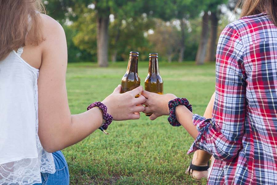 Female college students clinking bottles – alcohol abuse in the making?