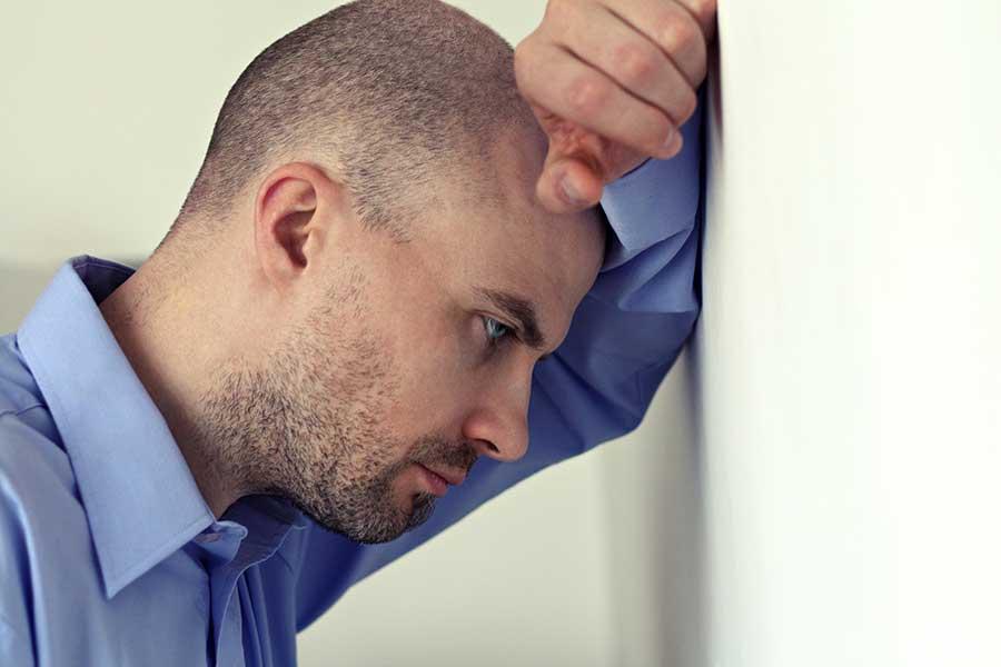 Despairing man with head wall struggling with a crystal meth addiction