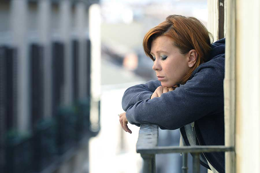 Depressed woman looking out balcony doesn't have to ask, what is addiction?